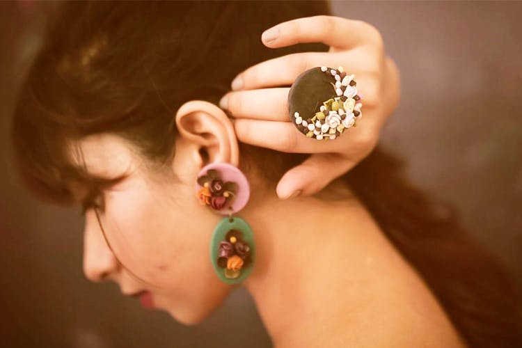Ear,Nail,Finger,Skin,Fashion accessory,Jewellery,Yellow,Body jewelry,Hand,Organ