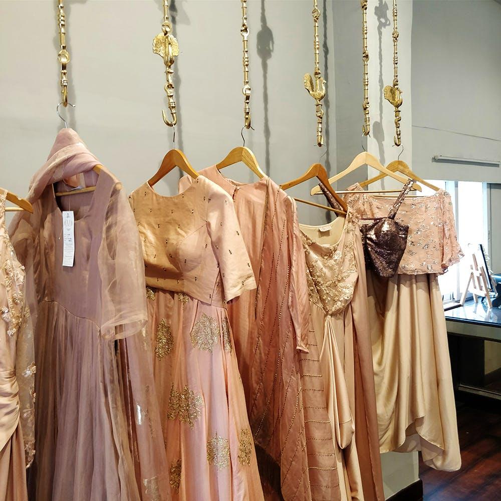 Clothes hanger,Clothing,Room,Boutique,Dress,Textile,Peach,Home accessories,Fashion design,Furniture