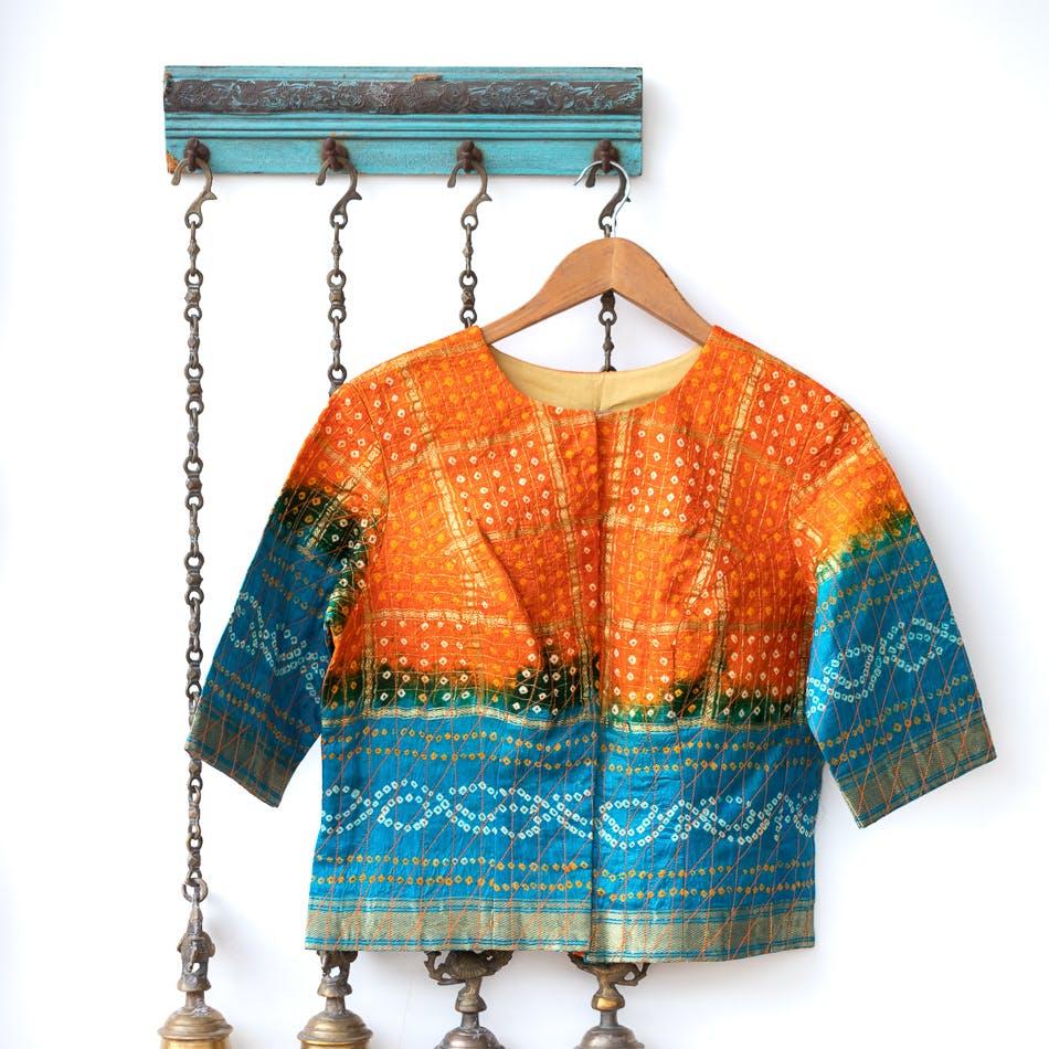 Clothing,Orange,Blue,Turquoise,Aqua,Outerwear,Sleeve,Neck,Clothes hanger,Blouse