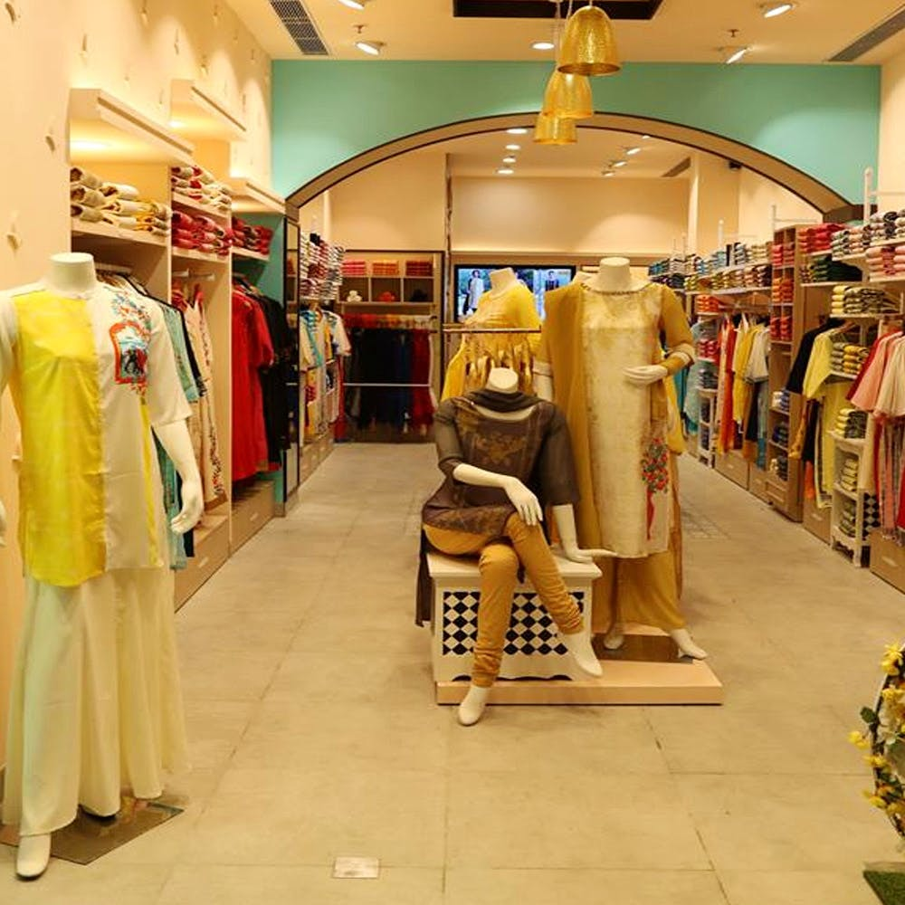 Boutique,Shopping mall,Outlet store,Yellow,Retail,Shopping,Building,Outerwear,Room,Mannequin