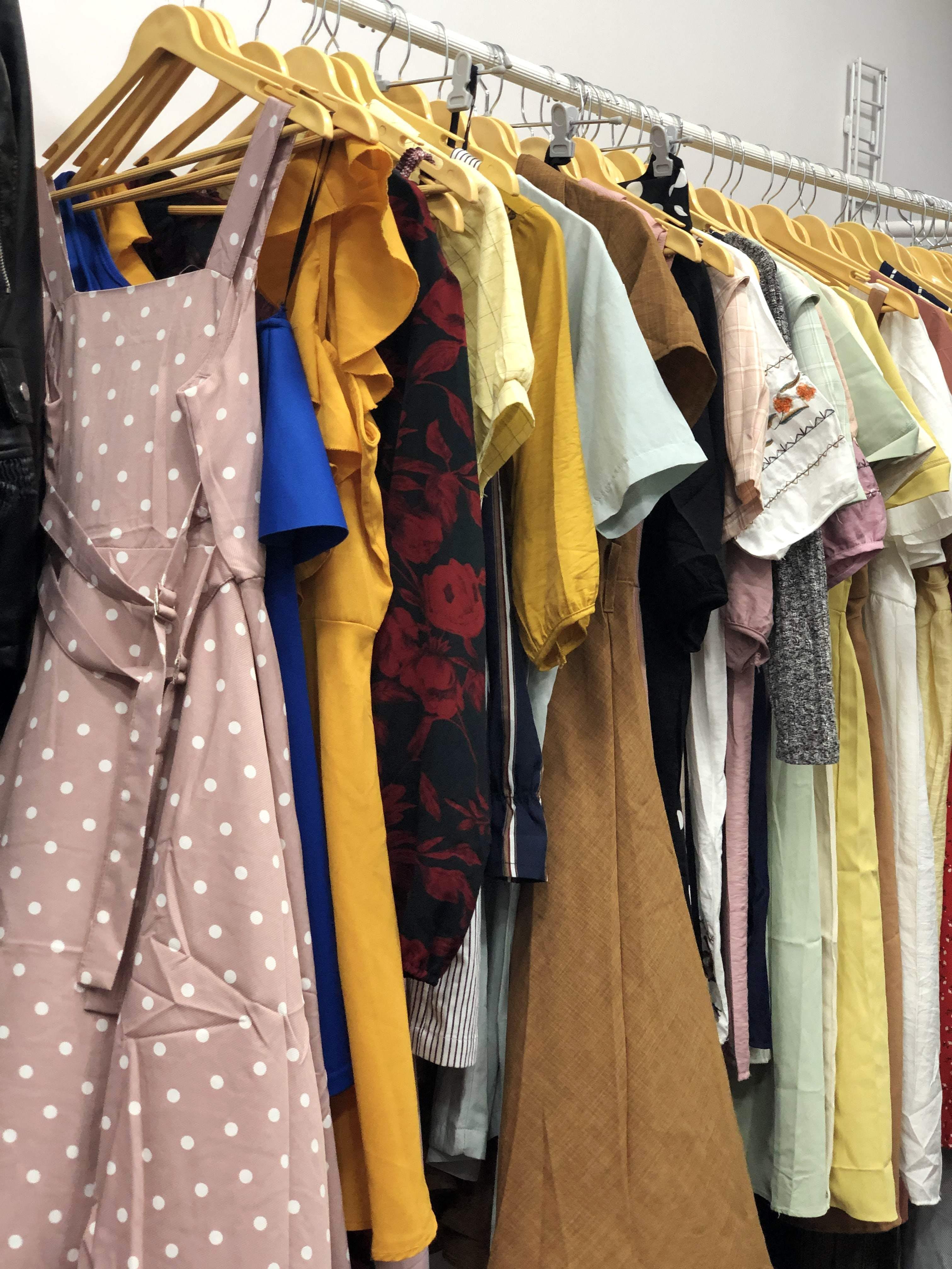 Clothes hanger,Clothing,Boutique,Yellow,Room,Outerwear,Textile,Dress,Fashion design,Costume design