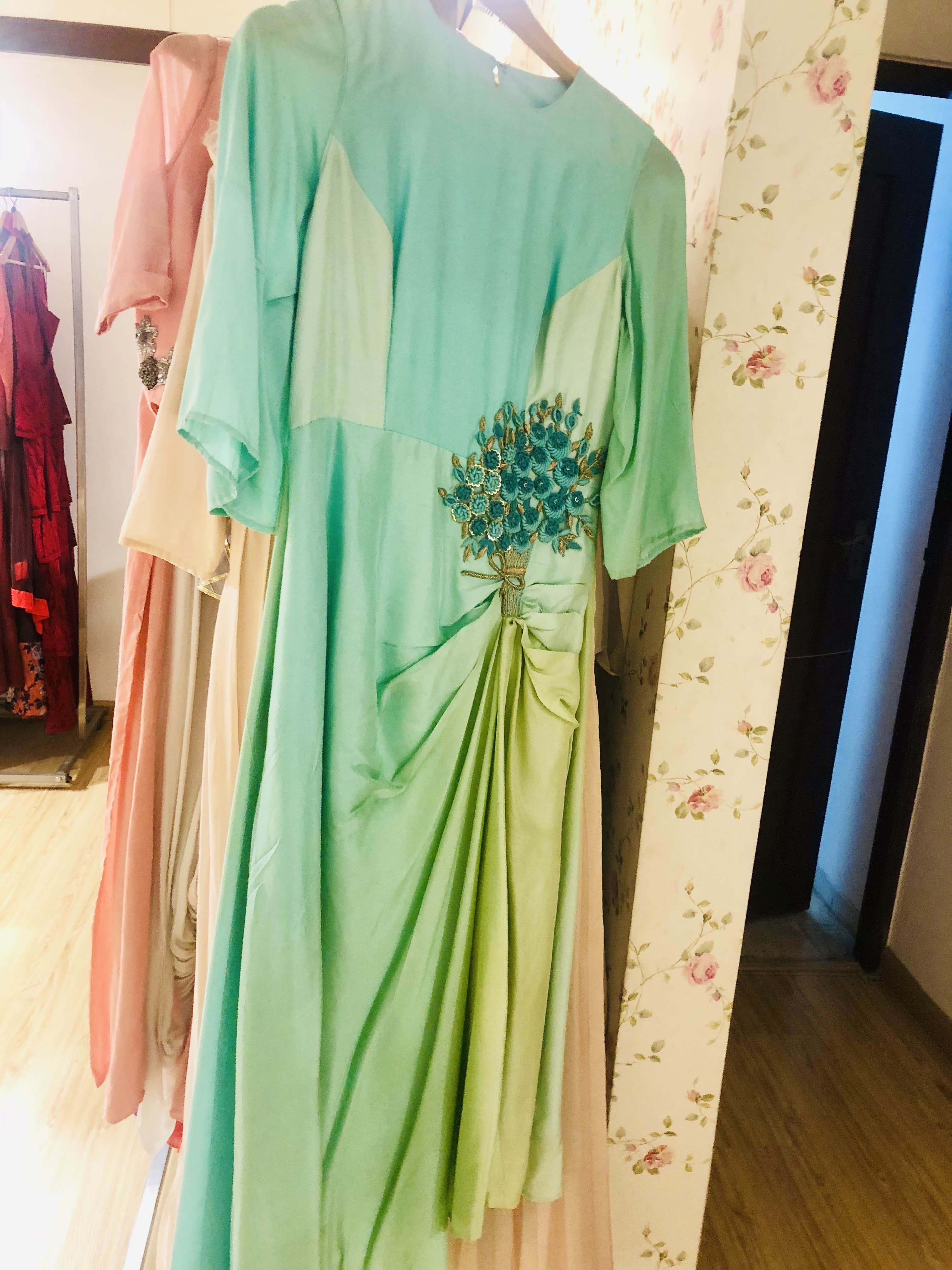 Clothing,Green,Dress,Formal wear,Boutique,Fashion design,Shoulder,Room,Outerwear,Textile