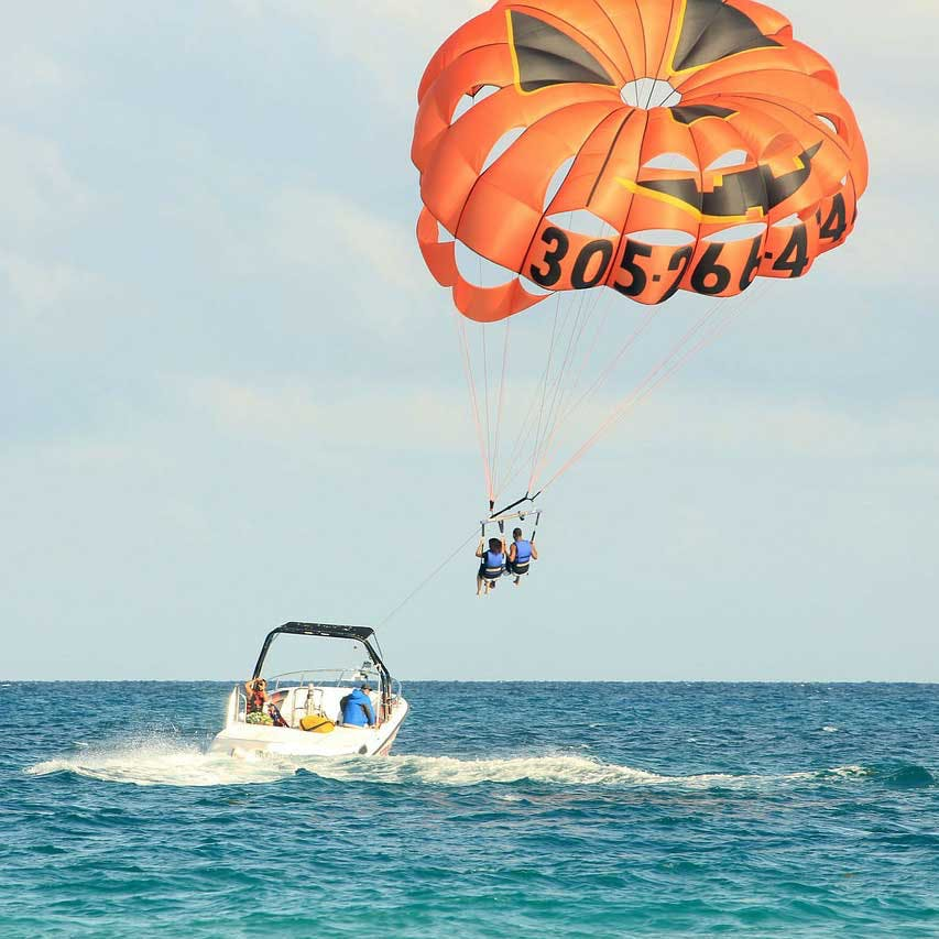 Parasailing,Parachute,Kite sports,Surface water sports,Water sport,Windsports,Sky,Vacation,Fun,Towed water sport