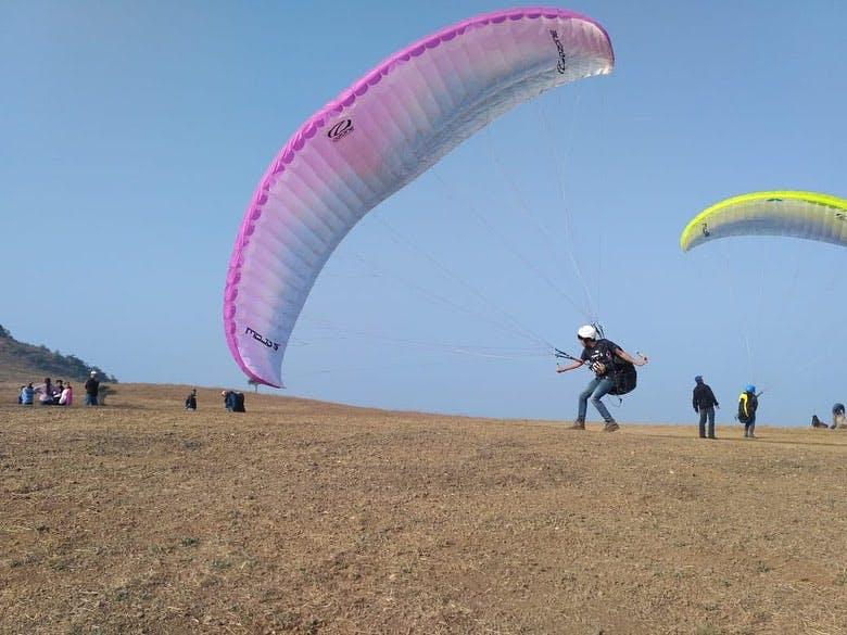 Parachute,Paragliding,Air sports,Parachuting,Windsports,Natural environment,Sky,Pink,Fun,Kite sports