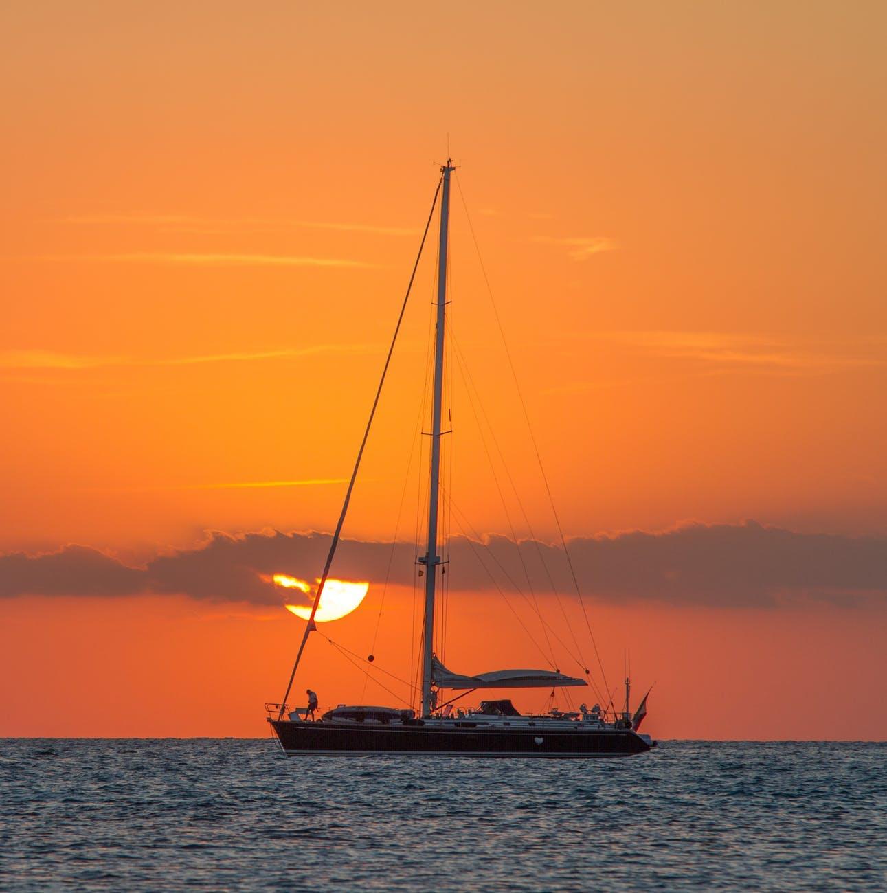 Boat,Vehicle,Sky,Sunset,Calm,Sailboat,Watercraft,Dhow,Sailing,Orange