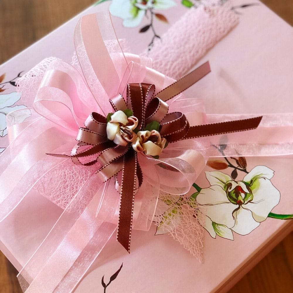 Pink,Ribbon,Party favor,Wedding favors,Gift wrapping,Cut flowers,Flower,Present,Wedding ceremony supply,Plant