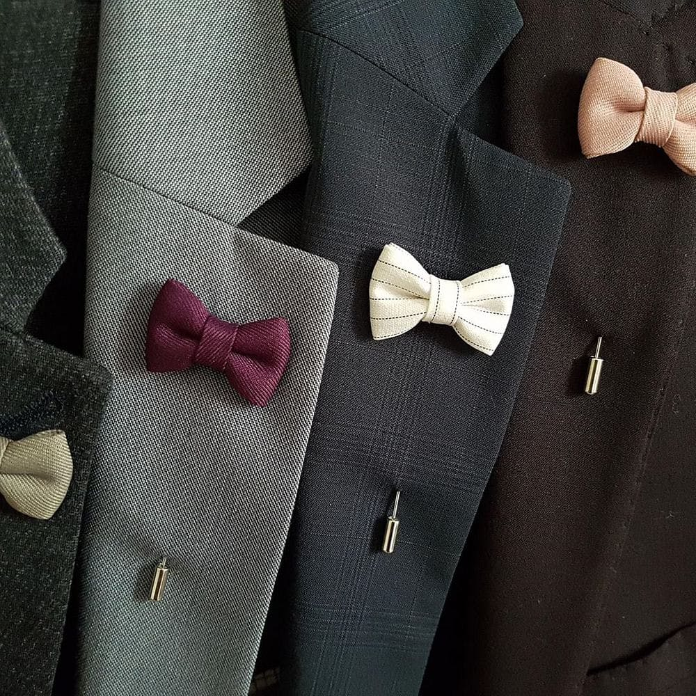 Tie,Bow tie,Formal wear,Suit,Tuxedo,Fashion accessory,Button,Pocket,Knot