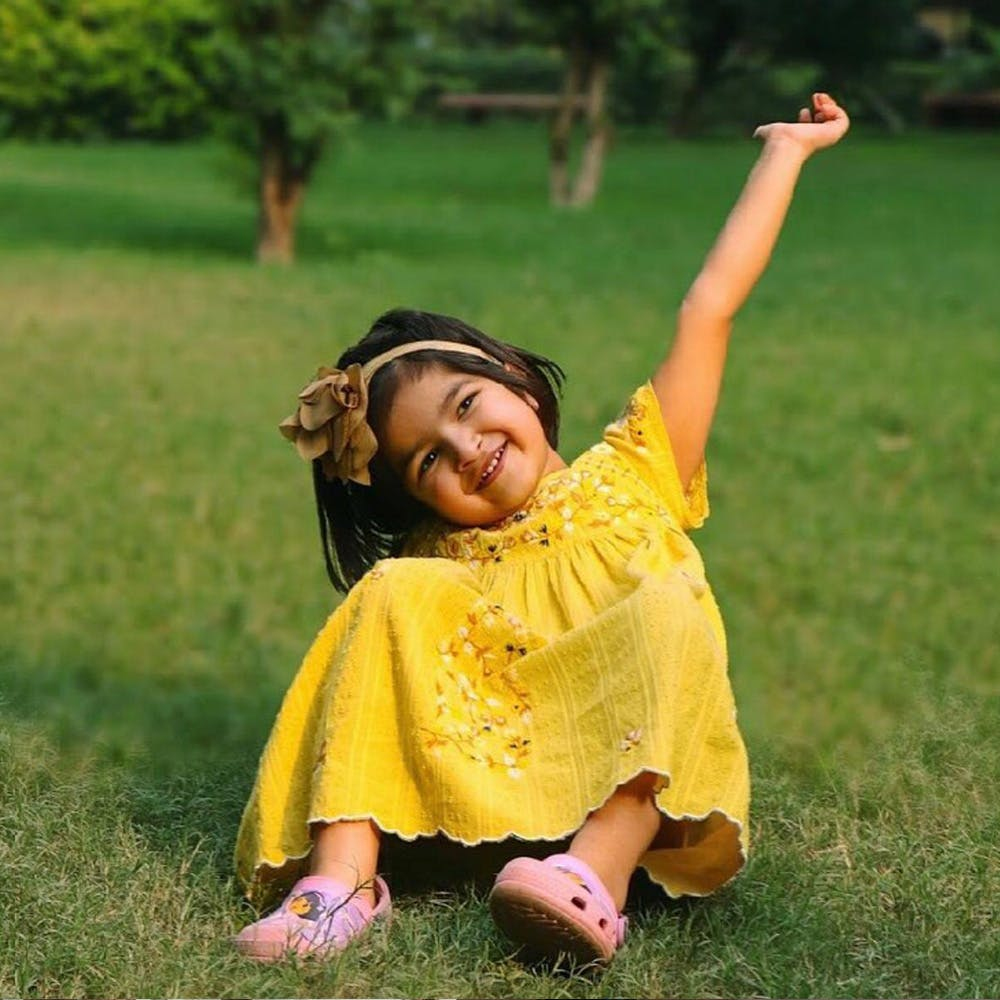 People in nature,Facial expression,Yellow,Grass,Happy,Smile,Fun,Arm,Lawn,Meadow