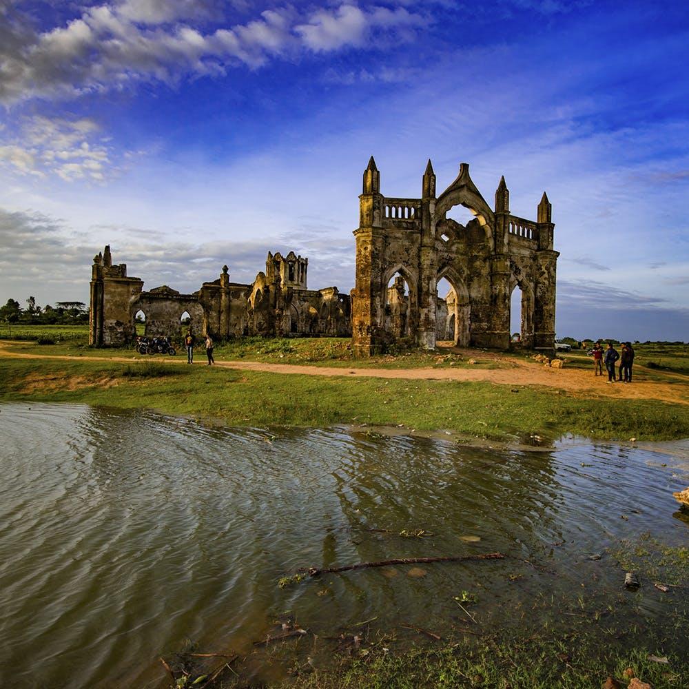 Sky,Reflection,Natural landscape,Architecture,Cloud,Building,River,Church,Ruins,Grass