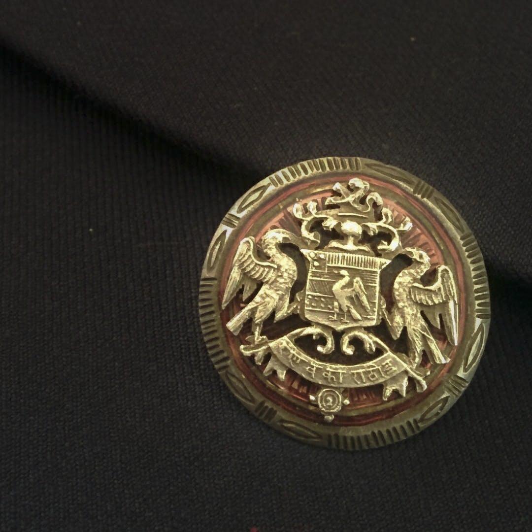 Badge,Font,Symbol,Circle,Emblem,Crest,Metal,Pattern,Fashion accessory,Logo